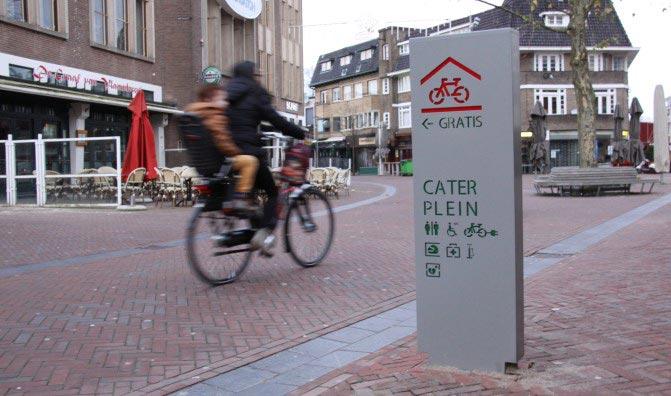 de zuil verwijst naar de gratis fietsenstalling bij het caterplein de bedoeling is om de fietsers te stimuleren hun fiets in de stalling te plaatsen en